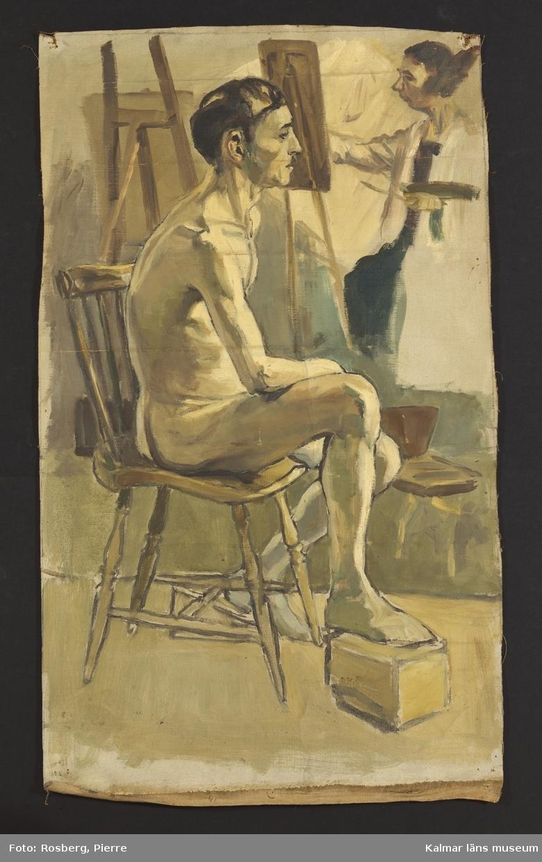 Mörkhårig manlig nakenmodell som sitter på en brun pinnstol, han har ena foten på en låda som står på golvet. I bakgrunden står en kvinna vid ett staffli och målar.