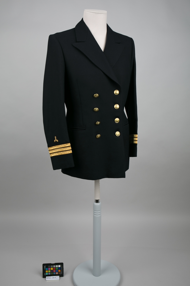 Førstemaskinist uniformjakke med 3 stk. gullbånd og påsydde distinksjoner på erme og slag krage. Dobbelspent med til sammen 8 stk. knapper i gullfarge med motiv av anker.