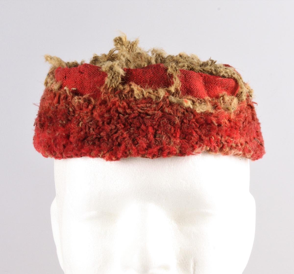 """Rester av topplue strikket i høyrødt garn. Lua er glattstrikket fram og tilbake (5 masker pr cm) og er sammensydd i nakken. 7 cm dobbel kant med bukt øverst og antakelig også nederst. Brettekanten er festet ned med noen sting i forkant. Inni er kanten flosset med rød tråd. Antakelig har hele lua vært rød utenpå, men det er strikket fôr i hvitt (gulgrått?), her er maskene grovere og løsere. Selve lua kan være maskinstrikket. Kilde Ragnhild Bleken Rusten, Totn årbok 1994. Kommentar (RBR): Kan dette være et eksemplar fra Mykkby Manufakturen? Les bygdebok for Stor Elvdal av Fosvold. Manufakturen gikk under navnet """"Enigheten""""."""