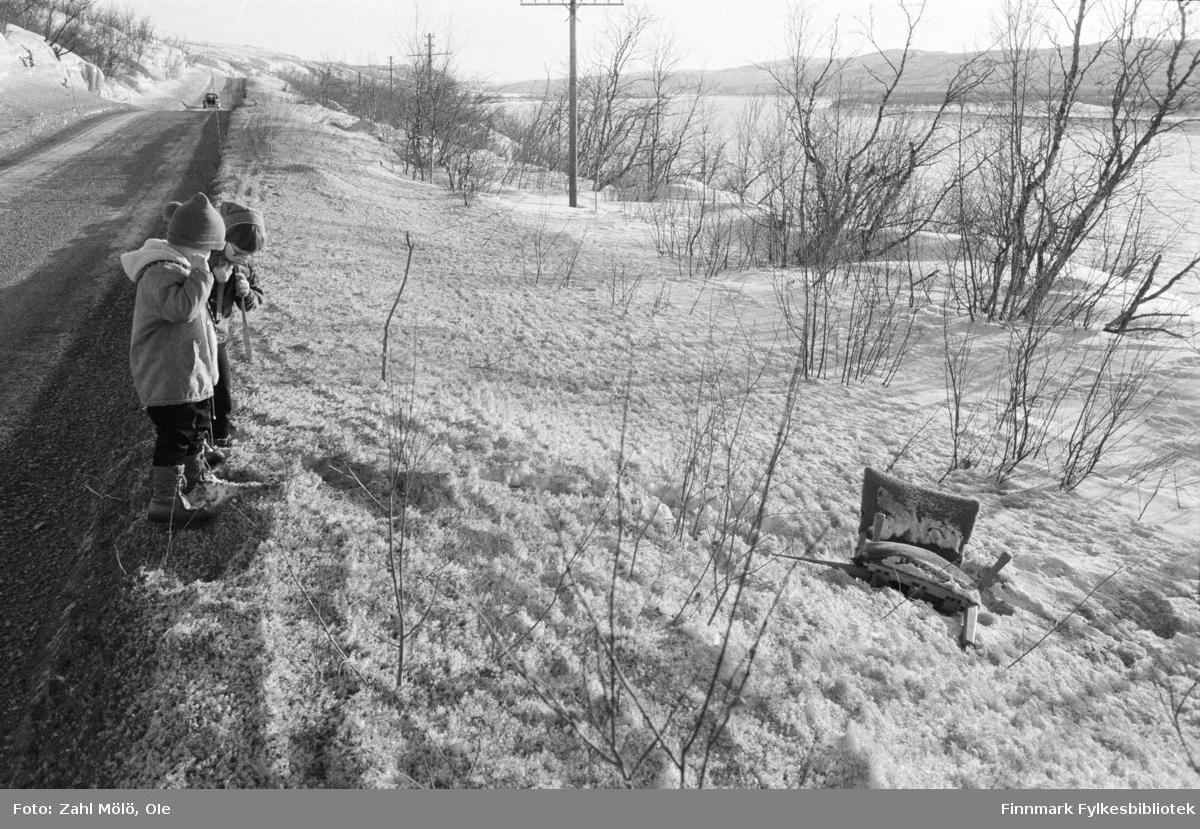 Vår i Tanadalen. To barn ved veikanten mellom Skiippagurra-Polmak. En lenestol er kastet på bakken i snøen. Tidspunkt er rundt 1970.