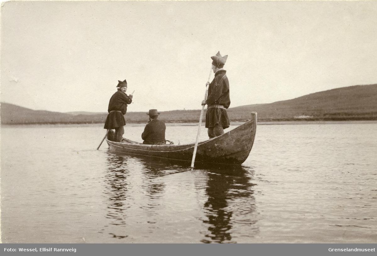 Staking av elvebåt ved Seida, Tana. Andreas Bredal Wessel sitter midt i båten og to ukjente koftekledte menn staker.