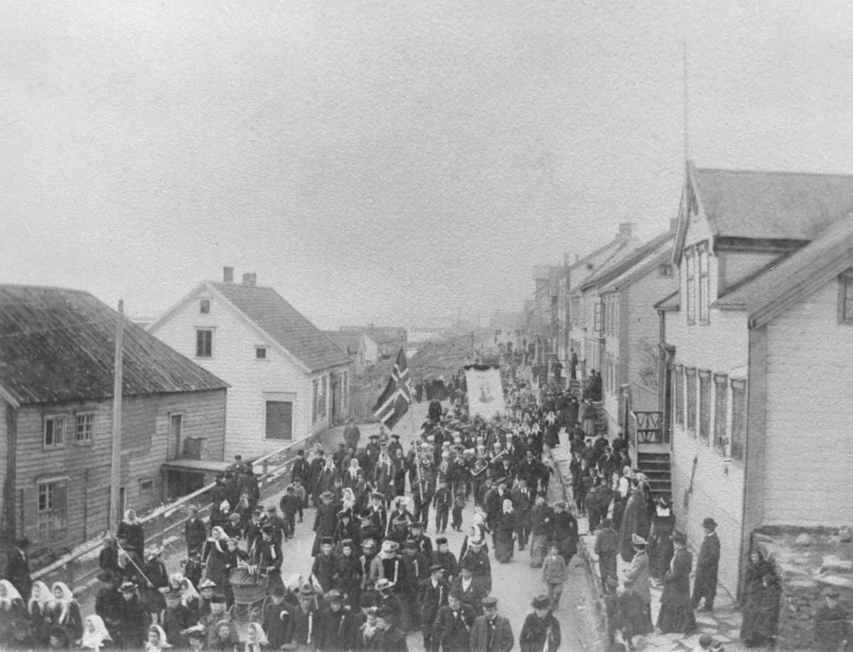 17. mai-tog i Vadsø i 1905 med flagg og musikkorps. Sivertsengården (Ekviperingen) til høyre.