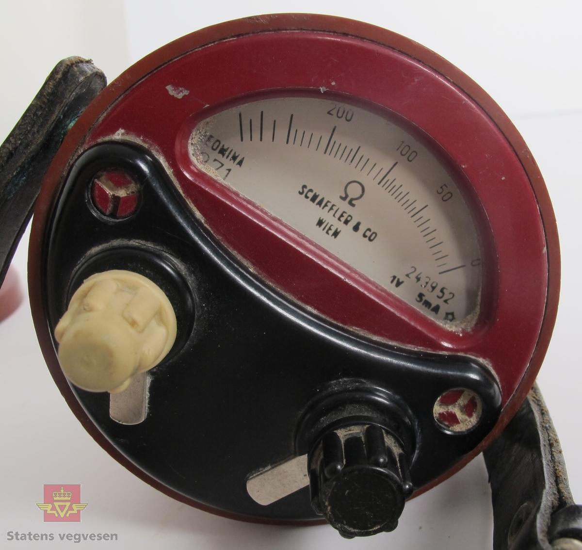 Ohmmeter i burgunderrødt hus av metall, dekket med gummi. Har to tilkoblingspunkter for ledning og bærereim av lær. Målevindu med nål som viser verdier fra 0 til 500 ohm. Har innskrift på lokket SCHAFFLER & CO, WIEN og påskrifen DREMONIA 1971 SCHAFFLER & CO WIEN 243952 1V 5 mA i målevinduet på ohmmeteret.
