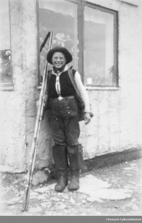 En gutt med fiskestang i hånden og ryggsykken i ryggen ved siden et hus, muligens i Salttjern.
