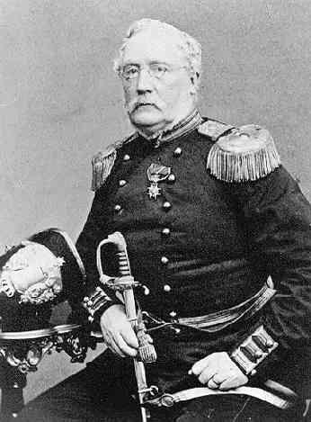 Porträtt av en man med mustasch och glasögon. Han är klädd i militär uniform och sitter i en stol och vilar höger arm på ett runt bord intill. Han håller handen på sin värja och på bordet ligger hans kask.