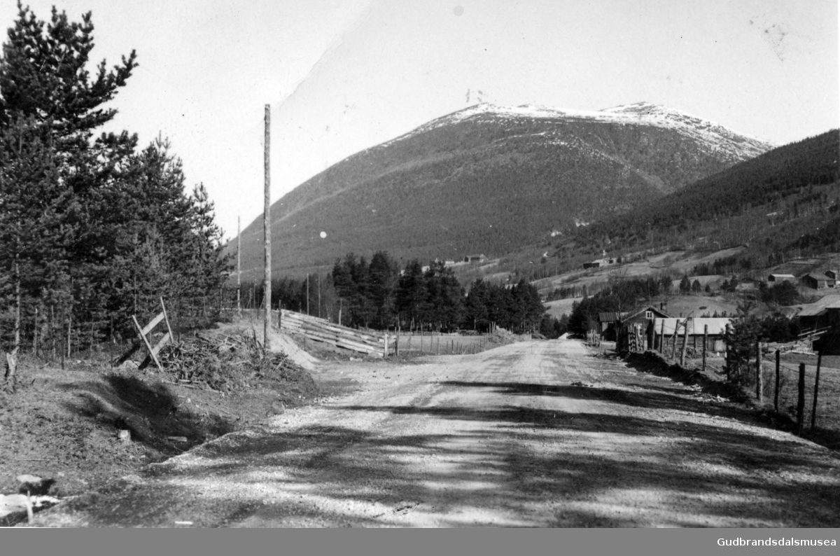 Nordover langs hovudvegen på Dovreskogen. Ein ser Akerjordet på høgre side av vegen. På andre sida av elva ser ein frå venstre Rødølen, Breidalen og Haugen. I bakgrunnen Veslfjellet.
