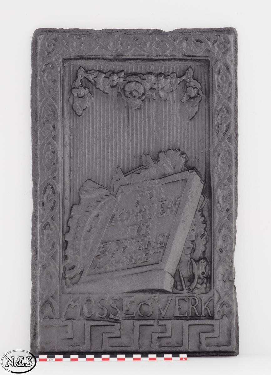 Ovnsplaten er en kortside - 1. etg. Ovnplaten har riflet bunn med ramme av båndfletting på tre av siden. Nederst på platen er en meanderbord. Krigerske emblemer er delvis skjult av plate med innskrift. Over henger en blomstergirlande.