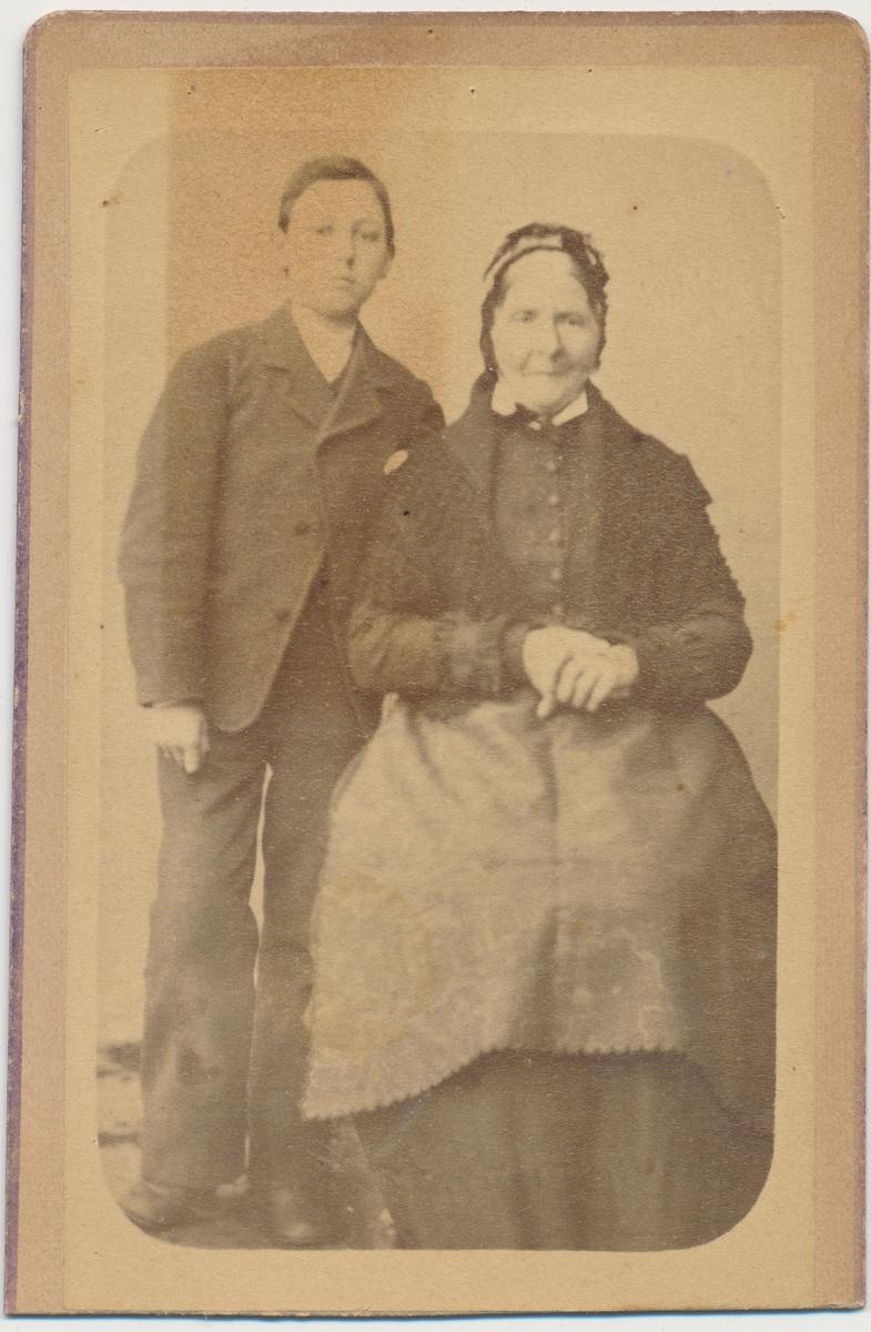 Helfigur foto av sittende eldre kvinne og stående ung gutt, ukjente