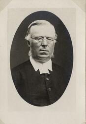 Porträttfoto av en medelålders man med glasögon, klädd i prä