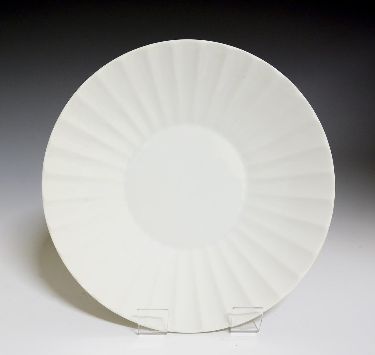 Prot: Litet fat av porselen. Fanen skrå med svakt buet side, som har nedsenkede radiære felt. Hvit glasur, uten dekor.