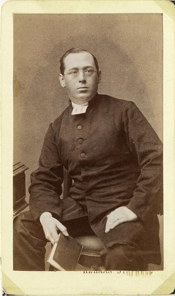 Foto av en man i glasögon, klädd i prästrock och prästkrage m.m. Han håller en bok i ena handen.  Knäbild, halvprofil. Ateljéfoto.