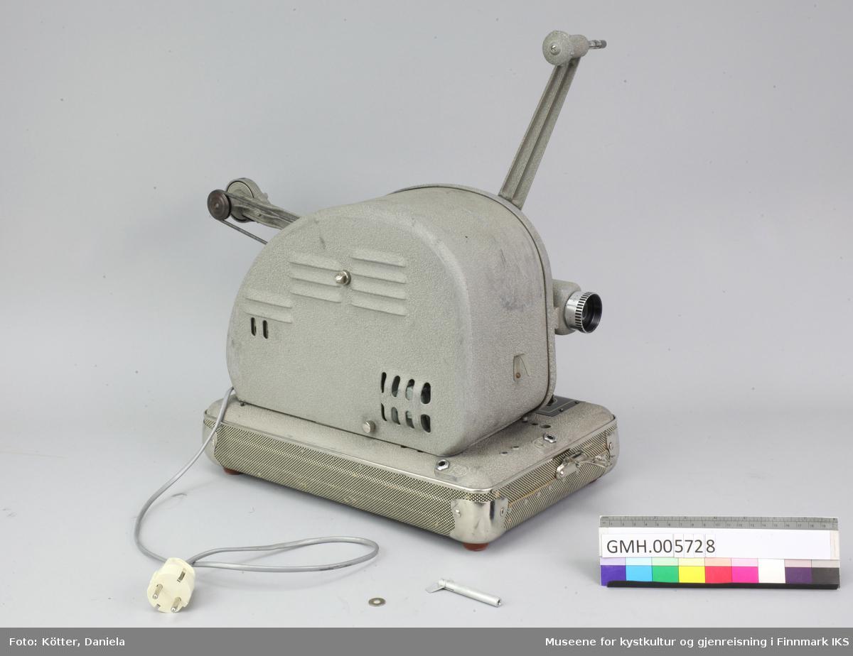 Fremviseren har en avrundet, grå korpus med spolearmer som kan klaffes ut. Den står på en base som også danner bunndelen av emballasjen. For transport, settes det en hette over apparatet. Hetten er av stødig, grønn-mønstret pappmateriale som er stiftet i sømmene og forsterket med metallhjørner, lik en koffert. I hetten er det montert et høyttaler og en audiokabel på en kabelrull som kan knyttes til fremviseren. Hetten festes til bunndelen med to lås på kortsidene. På overside er det et bærehåndtak. Apparatets lys og lyd fungerer, men ikke motoren. Dette må undersøkes, siden etiketten tyder på at den har fungert tidligere.