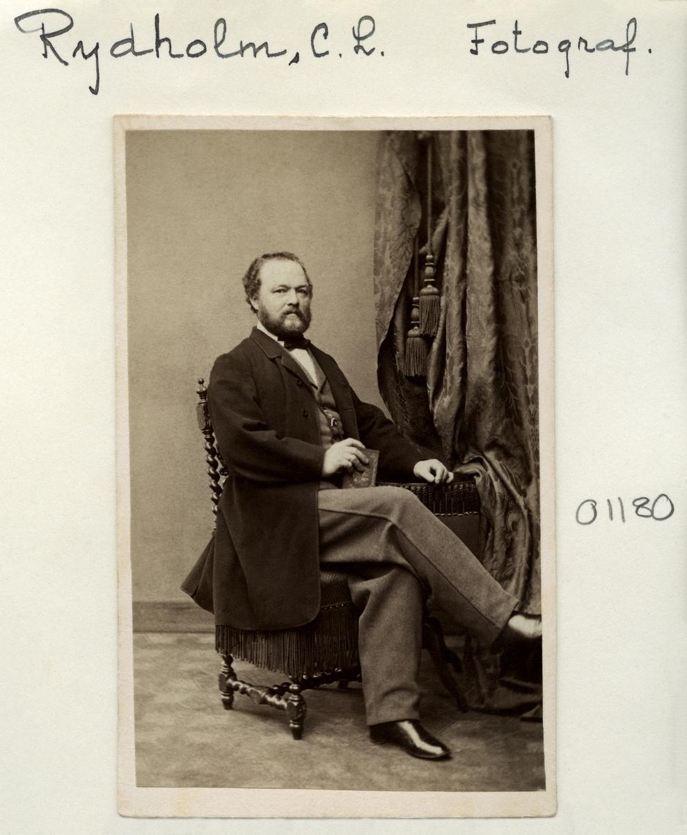 Porträtt av fotograf Svante Leonard Rydholm. Svante Leonard Rydholm var en relativt etablerad konstnär som anammat fotoyrket genom anhöriga i hemorten Uddevalla. Inflyttad till Linköping 1860 kom han till Linköping för att starta fotoverksamhet i änkefru Dahlmans trädgård, och blev därmed stadens andra fasta fotograf. Vidare drev han rörelsen från Kungsgatan 5 för att senare flytta till Ågatan 35. Han var framgångsrikt verksam i Linköping till 1882.