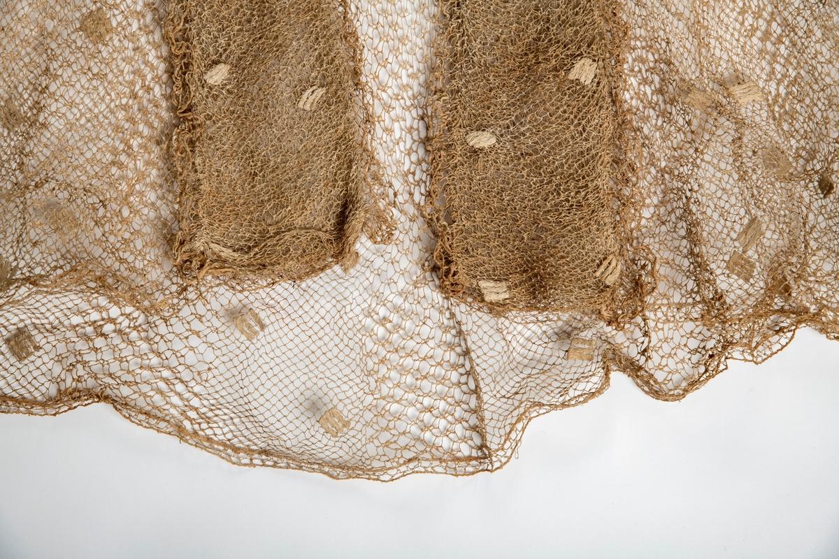 Grov knipling i fiskenettmønster, bestrødd med hvite romber. Kortermet. Bred krave som faller ned over skuldrene og ryggen. Åpen foran helt ned, med brede oppslag langs kanten av samme stoff lagt tredobbelt. Innsvingt i livet, køkappe bak. Har opprinnelig vært hvit, nå brun.