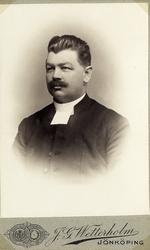 Foto av en man med mustascher, klädd i prästrock med prästkr