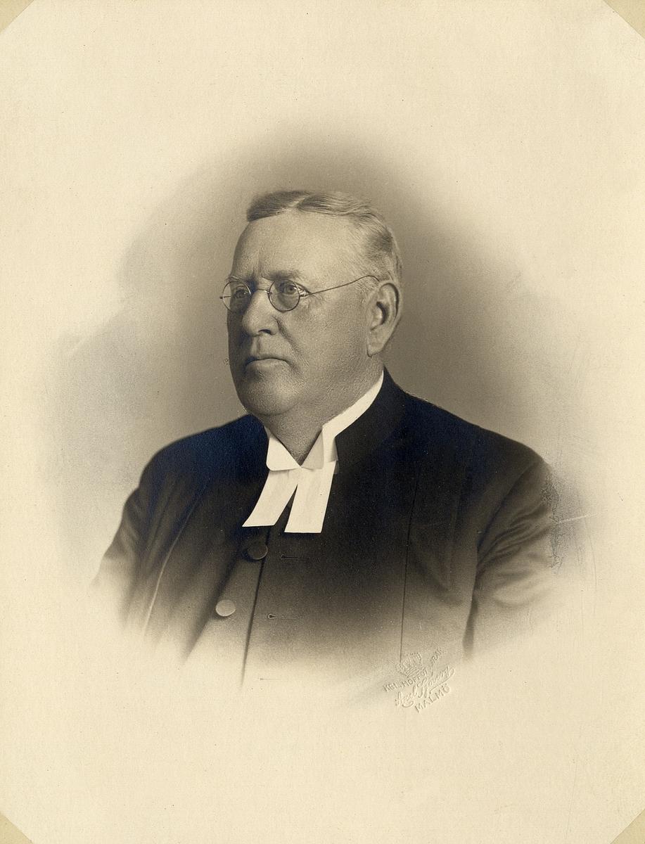 Foto av en man med glasögon, klädd i prästrock och prästkrage.  Bröstbild, halvprofil. Ateljéfoto.