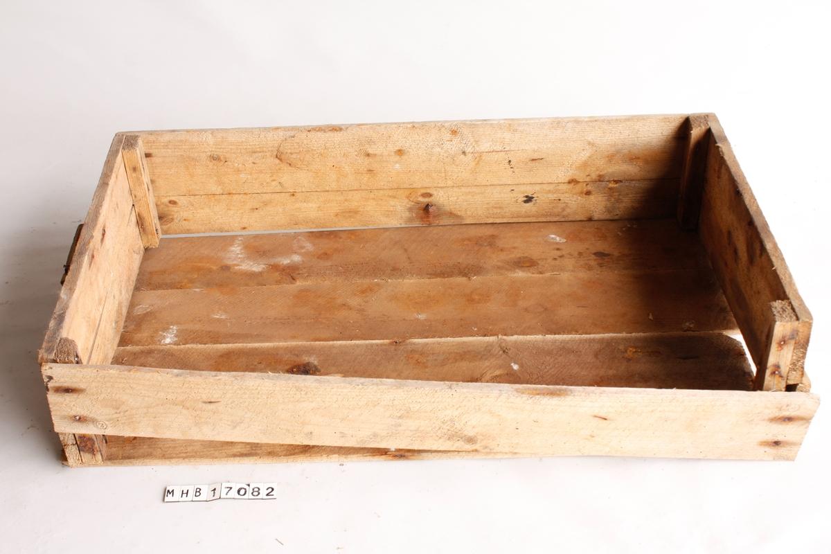 """Trekasse med diverse fiskeredskap og andre gjenstander. Rektangulær kasse bestående av fire bord i bunnen og to bord i høyden. Ett sidebord mangler. Bordene er spikret fast i treklosser i hvert hjørne. En trekloss er spikret fast i den ene kortsiden som håndtak. Alle bunnbordene er løse, ett av dem er trolig et opprinnelig sidebord.   Kassen inneholder - 16 søkkestein. 12 er av grønnlig kleberstein, med ulike flate former og et bearbeidet hull gjennom midten. Tre søkkestein består av rullestein med tynt tau surret rundt, og én stein er en kantet, naturlig stein med tykt hamptau knyttet rundt. Klebersteinssøkker ble benyttet til landnot og orkastnot. - Diverse taustumper i bomull og hamp. - 12 seftere (sefter: åregaffel) i ulike størrelser, trolig stål/jern belagt med sink eller aluminium. På to seftere er det festet tynne taustumper. - 11 tykke notringer i grønt metall (kobberlegering). Disse ble brukt til å snurpe sammen nota i bunnen før det ble vanlig å benytte patentlås. - Fem søkker. To søkker i rødlig leirgods, én flat og sirkulær med hull i kanten (""""pannestein""""), og én rundet og avlang med hull gjennom lengden. Tre små søkker av stein, to er dekket av brunt tekstil. Søkker i rødlig leirgods ble benyttet til seigarn (pannestein) og makrellgarn. - To ovale korkflå. Den ene er laget av kork og har en """"M"""" risset inn i overflaten. Den andre er laget av tre med """"MK"""" risset inn i overflaten.  - Ett treskaft til et redskap av jern (mangler). Skaftet er splittet på langs. - En kniv/fil av jern med trehåndtak. - En bunt med ståltråd. - Tre skiftenøkler i jern, ulike størrelser. To har hode i begge ender. - En bit av en skosåle med kanthull i brunt lær, og en brun lærbit. - En trekork. - Syv skruer og en mutter, trolig kobberlegering. - En rektangulær, bøyd metallplate, trolig sink. - Et tynt kobberrør. - Tre bolter i kobberlegering, to har rester av oransje maling og hampfibre ved hodet.  - En bolt med utstikkende kulehode, trolig jern belagt med sink. - Diverse deler,"""