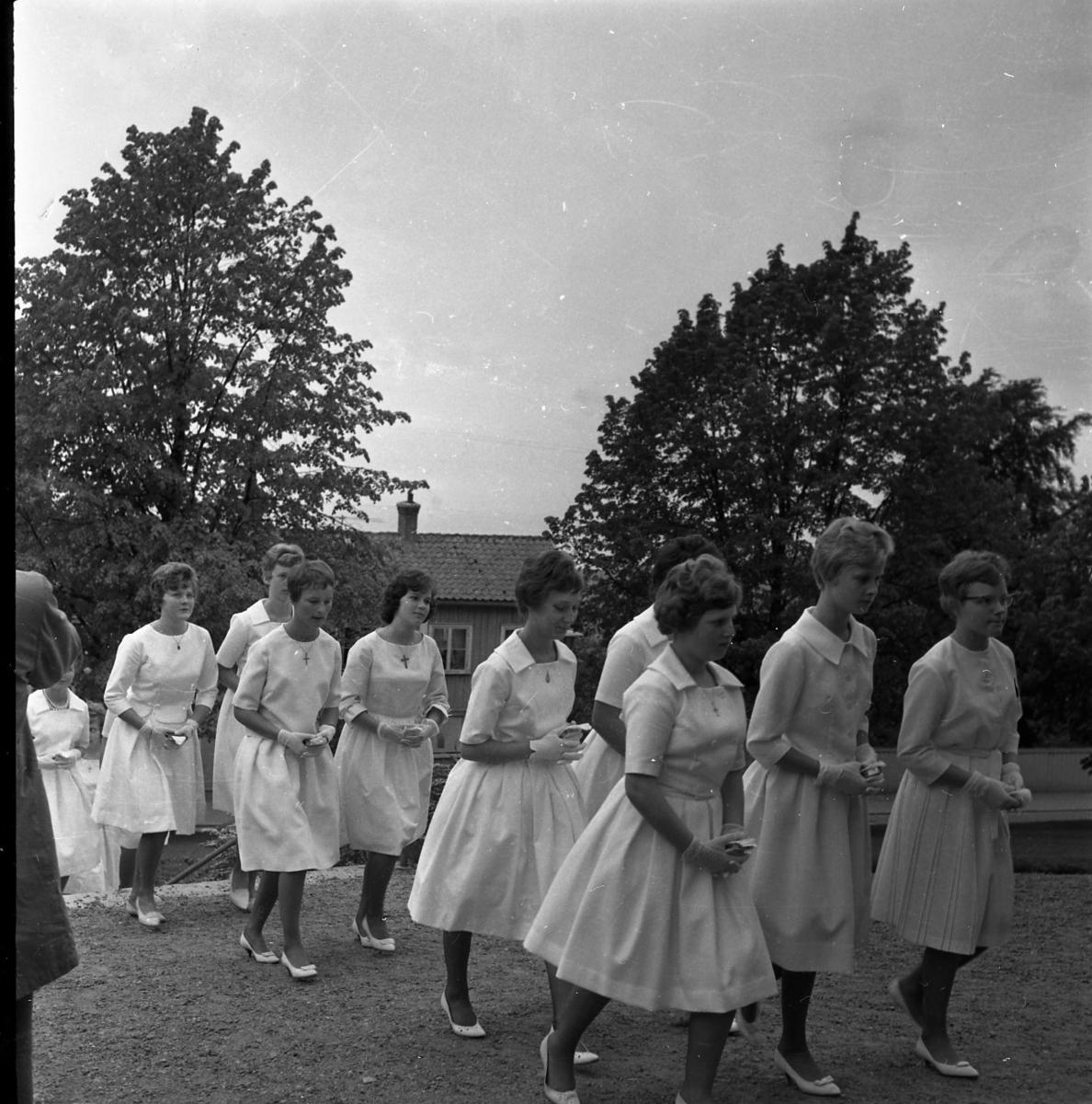 Kvinnliga konfirmander på väg in till Gränna kyrka.