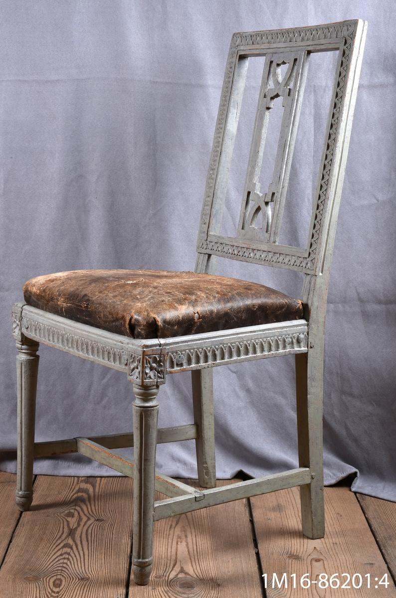 Gustavianska stol med svarvade framben med hörnfleuron och kanelyrer, raka bakben sarg och rygg med så kallad nagelskärning. Genombruten rygg med horisontell bricka så kallad Gunnebobricka, stoppad lös sits, klädd med oxhud.   Neg.nr: 81/1043:2