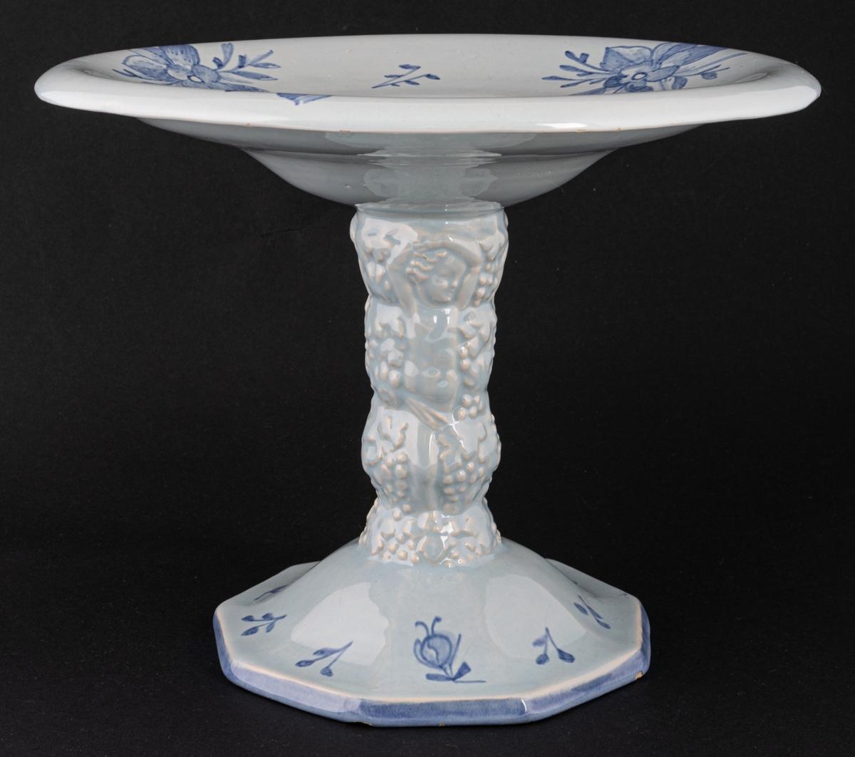 Skål med skulpterad fot, ljusblå med mörkare blå dekor. Tillverkad vid Bobergs Fajansfabrik i Gävle 1922-1924, formgiven av Gabriel Burmeister.