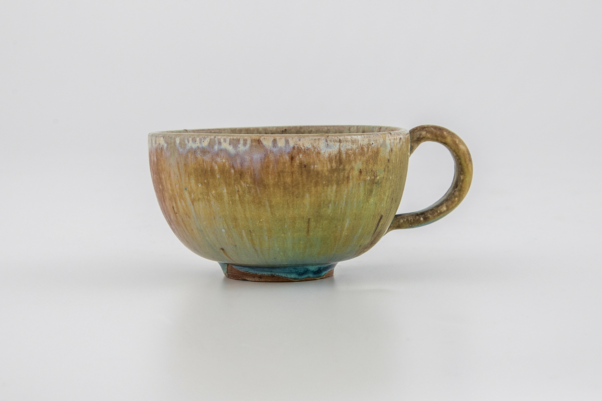 Kopp med skål i glasert steingods. Førstnevnte har påsatt hank. Både kopp og fat er dekket med en brun-grønn glasur som har rike fargevirkninger i form av blå, hvite, rosa og lilla innslag. På fatet er det små krystalliserte partier.
