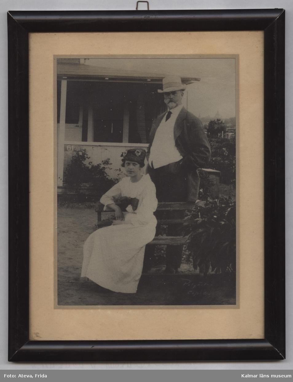 KLM 44200:5. Fotografi. Med passepartout i svart ram. Motivet föreställer föräldrarna Karl (född 22/1 1866, Farhult, död 29/12 1928, Kalmar) och Karolina (född 20/5 1864, Davide, Rone, död 2/8 1951, Kalmar) Kullzén. Polyfoto kopia. Han stående och hon sittande på en trädgårdsbänk. Båda med hatt. I bakgrunden en veranda.