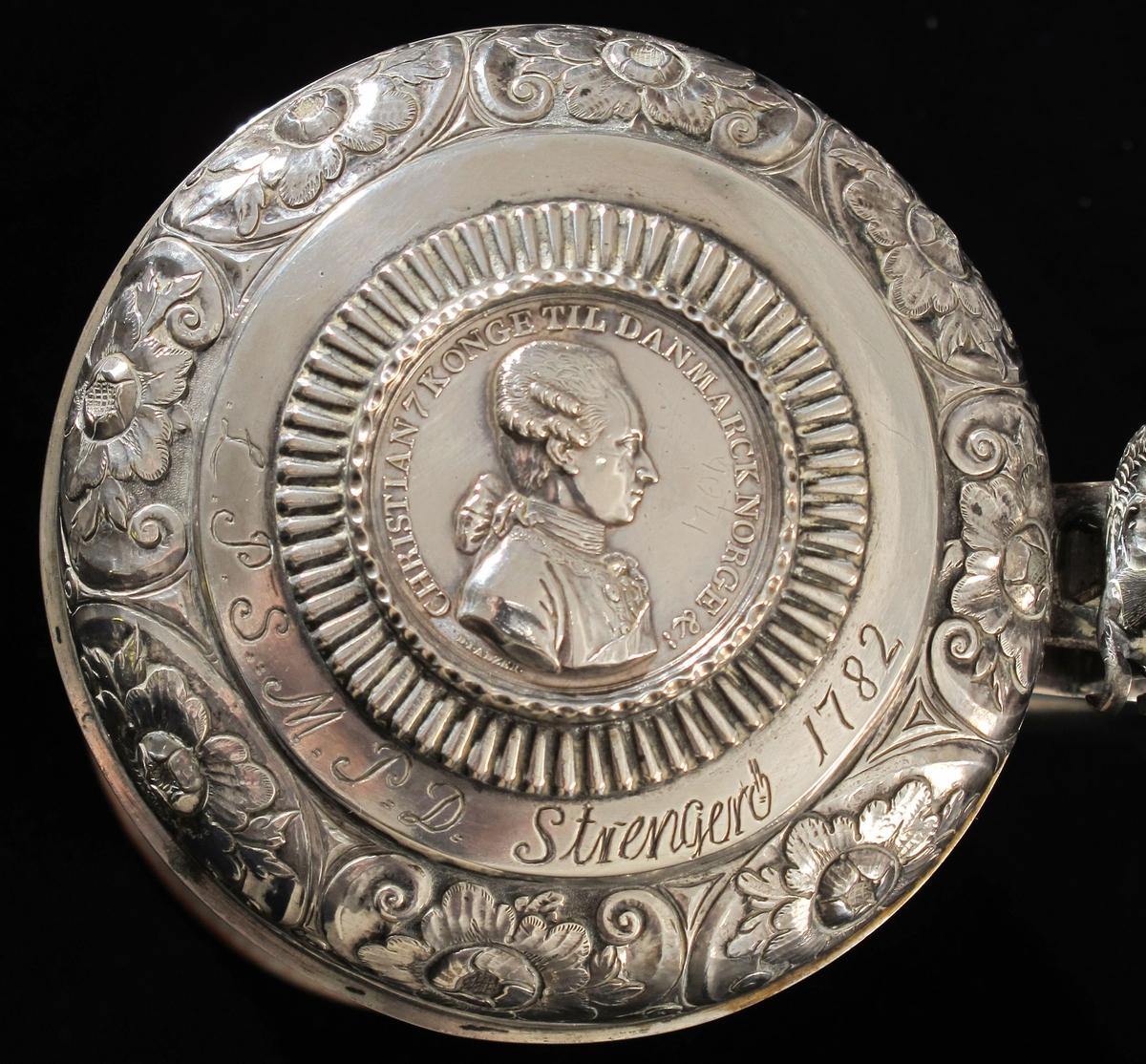 Polykrom blomsterdekor på kruset,  kongens portrett på medaljen. Havhest .