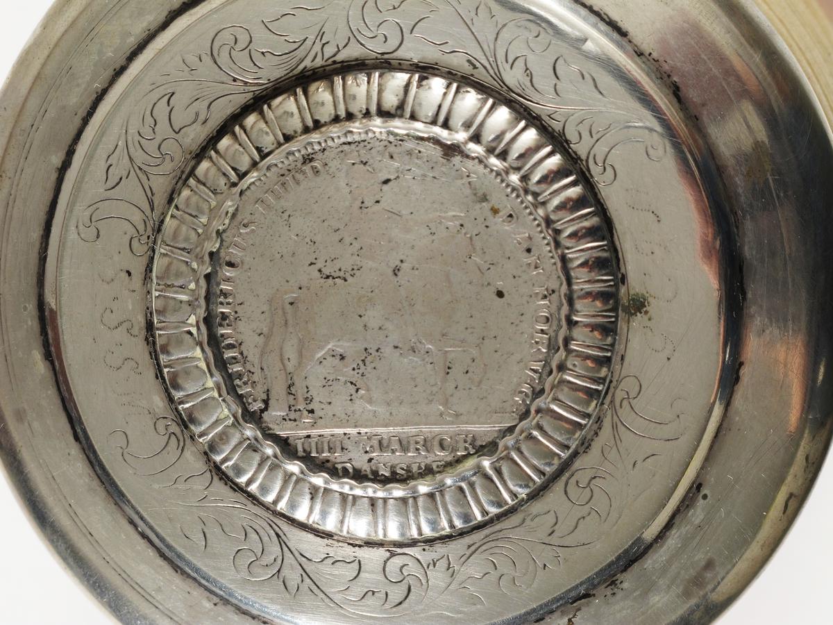 Stentøykrus m. lokk, sølv,  1700-årenes siste halvd.   Flatt lokk m. rundet profilert kant, innfeldt mynt  i radiært riflet innr., omgitt av akantusranke og  to felter  innr. av C-former hvori innprikket : SSSM,  og GCDM, lokkgrep som stående blad m. opprullede  fliker. Mynten 4 marck danske m. rytterfigur og innskrift:   FRIDERICUS IIII D G REX DAN NOR V G,  reversen riksvåben  m. krone og ordenskjede,  samt latinsk innskr. delvis  skjult:   DOMINUS MIHI AUDIUTOR , 1727?. Lokket montert på stentøykrus, sylindrisk, nederst  brunt rillet feldt, så glatt, derpå lyst, rillet  feldt, buet, profilert hank.