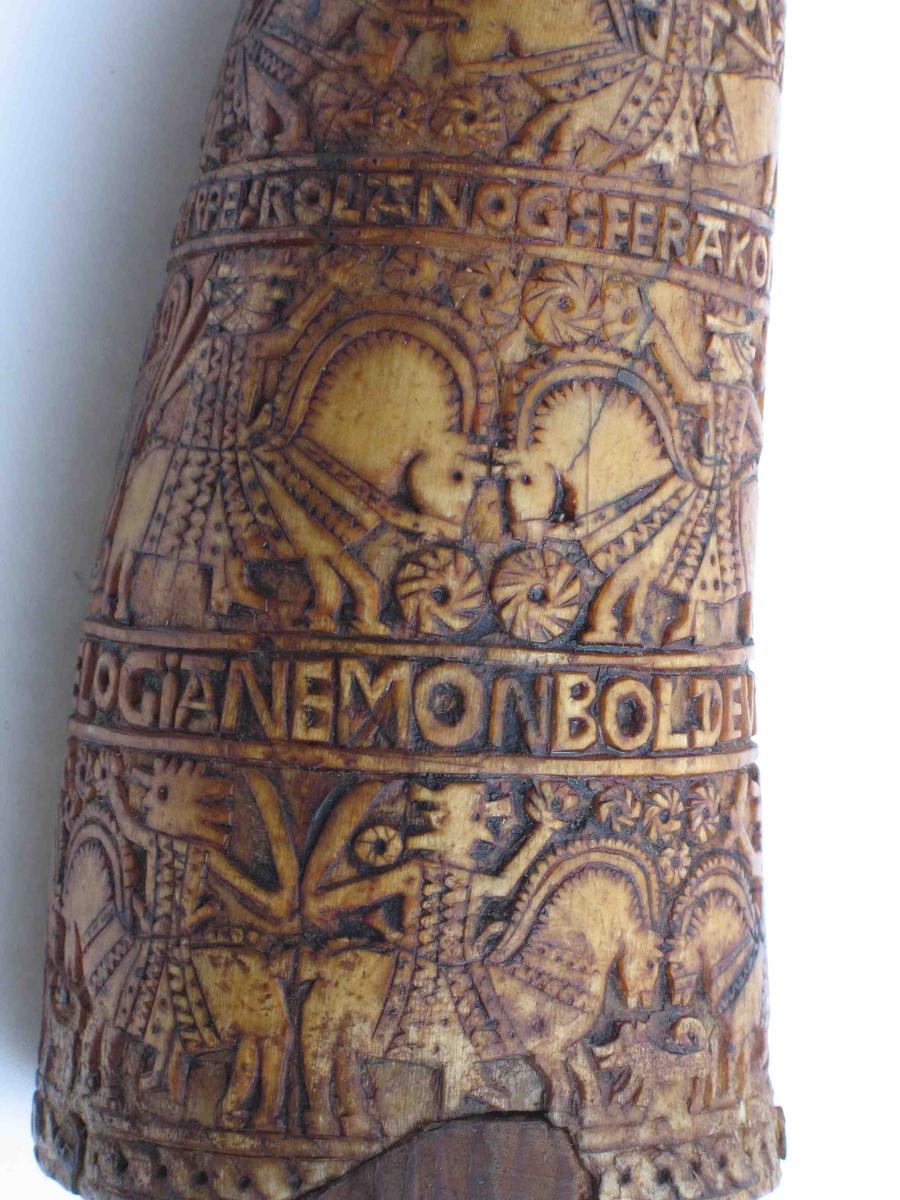 Rundt horn, toppen avskåret, vanlige små utskårne  felter og innskr.:   ADOMOGEVA PARADISTRE   DANNEL DRAGEN   OLGERDANSKEOGBVRIIAND ANN0 1723   DAVETHARPE: ROlANDOG-FERAKOND   KIESERKARELOGIANEMON   BOLDEVINDALKANNA   I bunnen ant. ny treplate hvorpå skrevet m. blyant:   L.E.M. 1870.  Tilst juni 1961: Sprukket på to steder, øverste del  avskåret, noe slitt i nederkant.