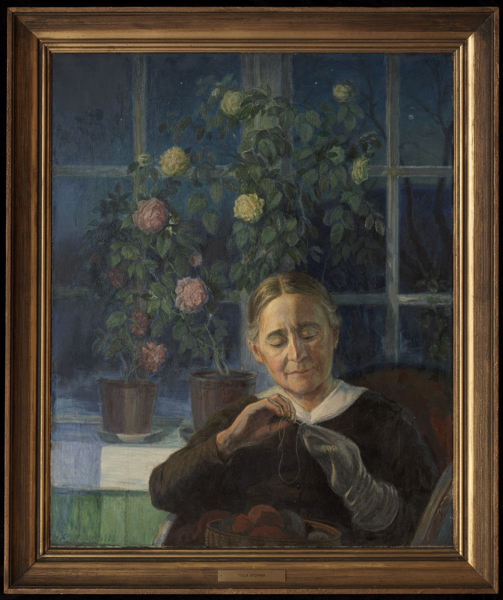 Tilla Valstad sittende i kubbestol, halvfig., frontal, stopper, brun kjole, i bakgr. vindu m. 2 rosentrær, blått utenfor