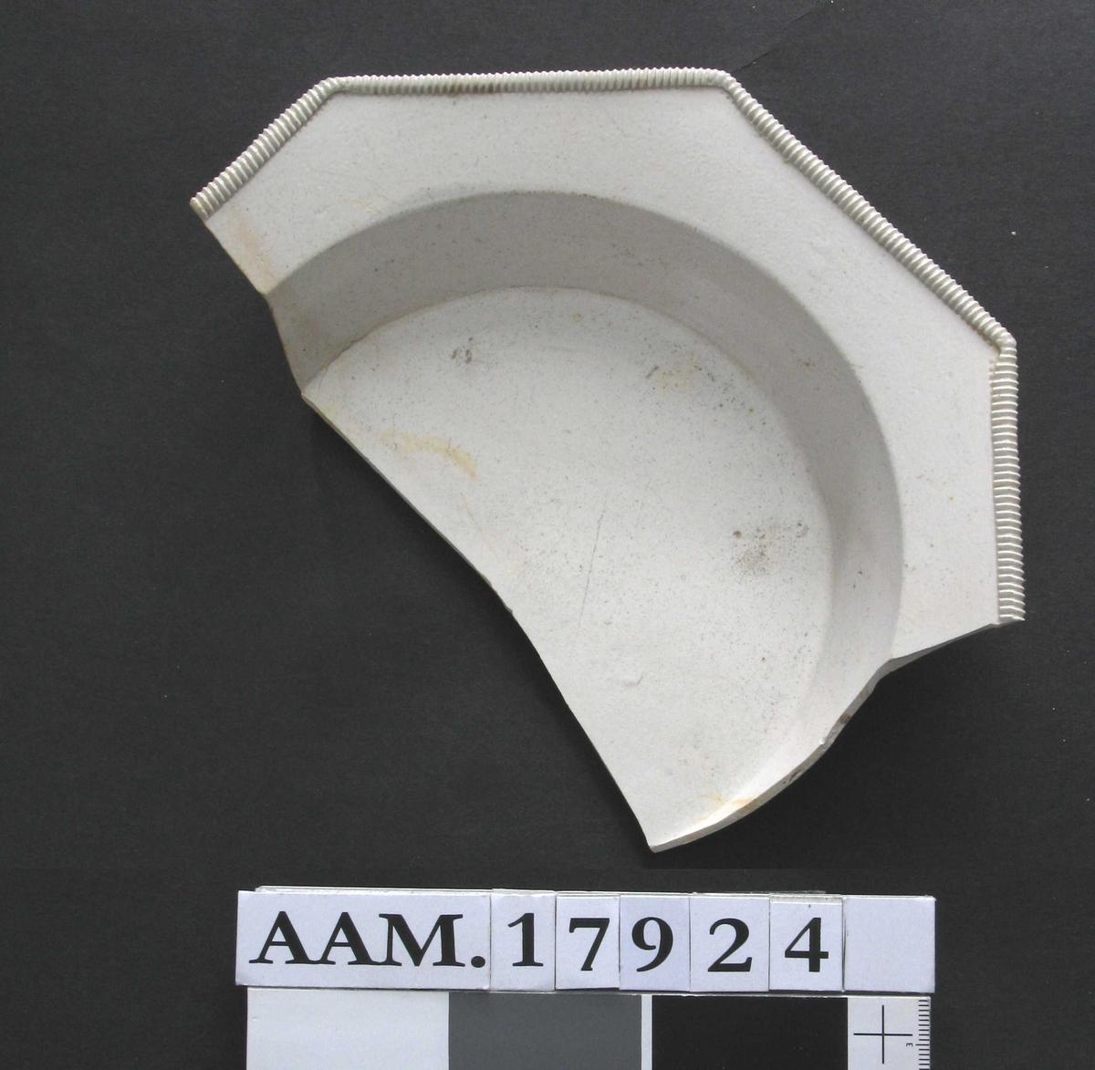 Del av tallerken, Staffordshire, 1770-årene. Stentøy,  saltglassert,  hårdbrent,  lyst grått gods, udekorert. Ustemplet.   skrå side, flat, svakt opppoverskrånende  brem, som er åttekantet  og med en tverr-riflet rund kantbord. Bunnkant.  Tilstand: ca. halve tallerkenen avslått  og et stykke til av bremmen.    Renset av Ib Kjølsen, brukt som  prøvemateriale for konservering av sjøfunn.