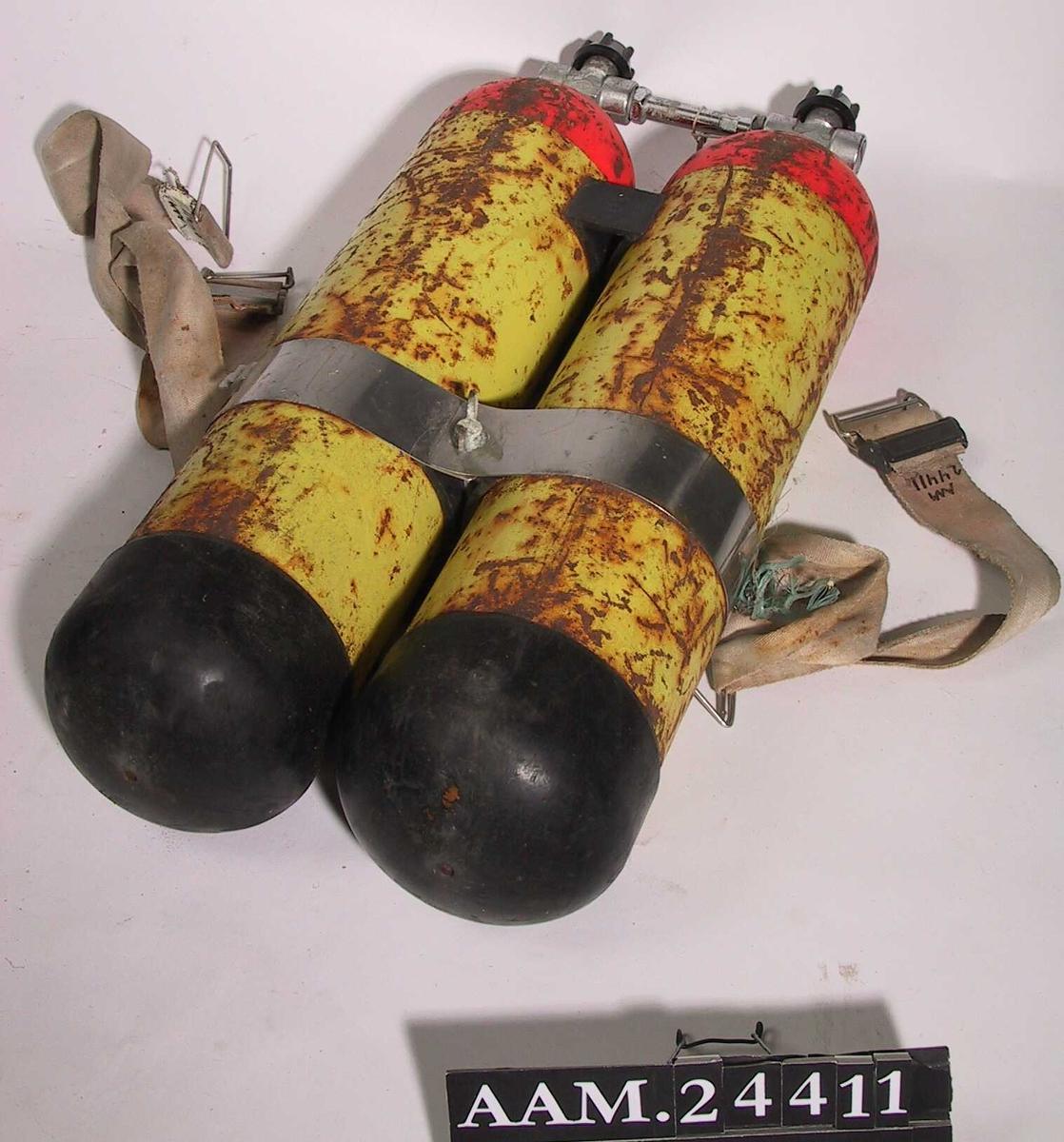 Dykkerflaske,  2 x 7 liter.  Jern, malt rød og gul, forkrommete kraner. Lerretsrem.  To gule   sylindre, sammenkoblet i den rødmalte øvre  ende med forkrommet rør og to kraner eller ventiler.  Over midten forkrommet bånd, skrudd sammen mellom  sylindrene, rundt bunnen er sort gummibelegg.  Tilstand: malingslitte, rustne.