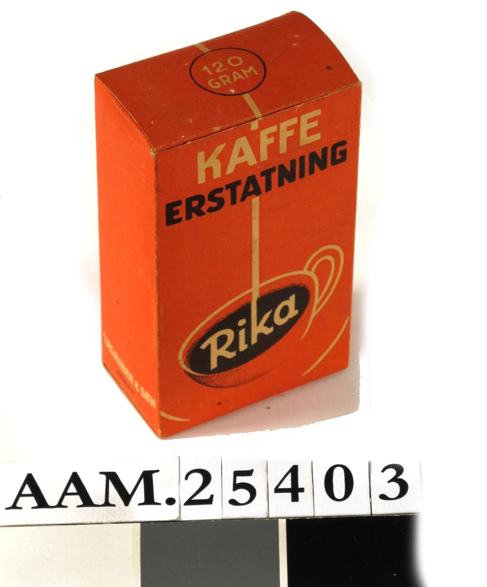 Eske m.trykt motiv og tekst, utstanset, brettet, limt.  Rødbrun, sort og hvit skrift. Pappesken inneholder en papirpose med kaffeerstatning.