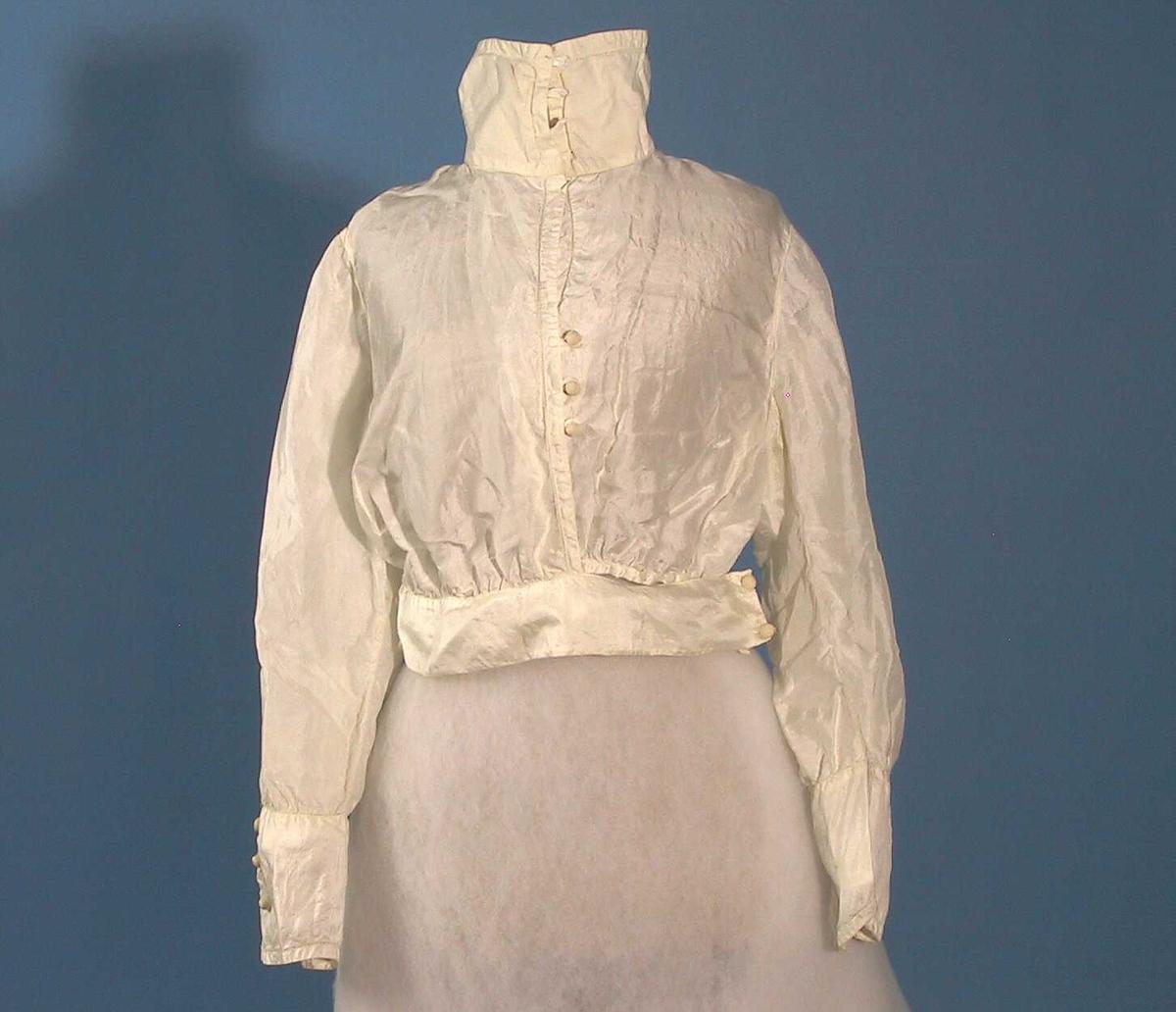 Hvit bluse med knepping foran, lange ermer, bred høy krage og brede armlinninger. Maskinsøm.