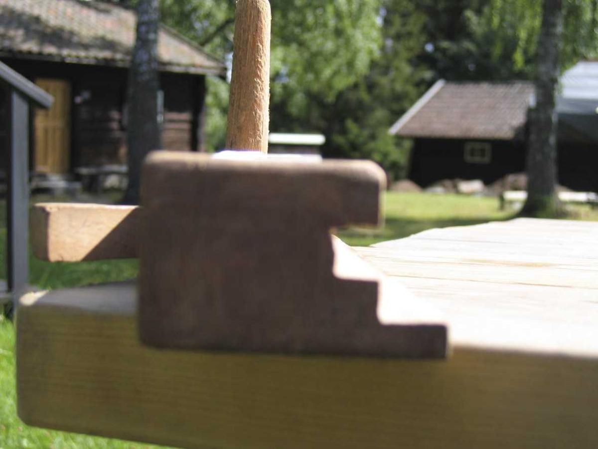 Kant + not som fjæra kan løpe i. Stålet magler. Framme er det et tverrgående håndtak av rundstokk.