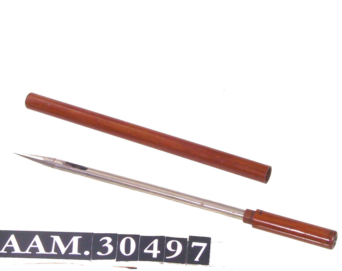 Form: Hult rør av metall med spiss i enden og spalte bak denne. Rør av tre fungerer som håndtak i motsatt ende, et tilsvarende trerør til å tre utenpå metallinstrumentet.