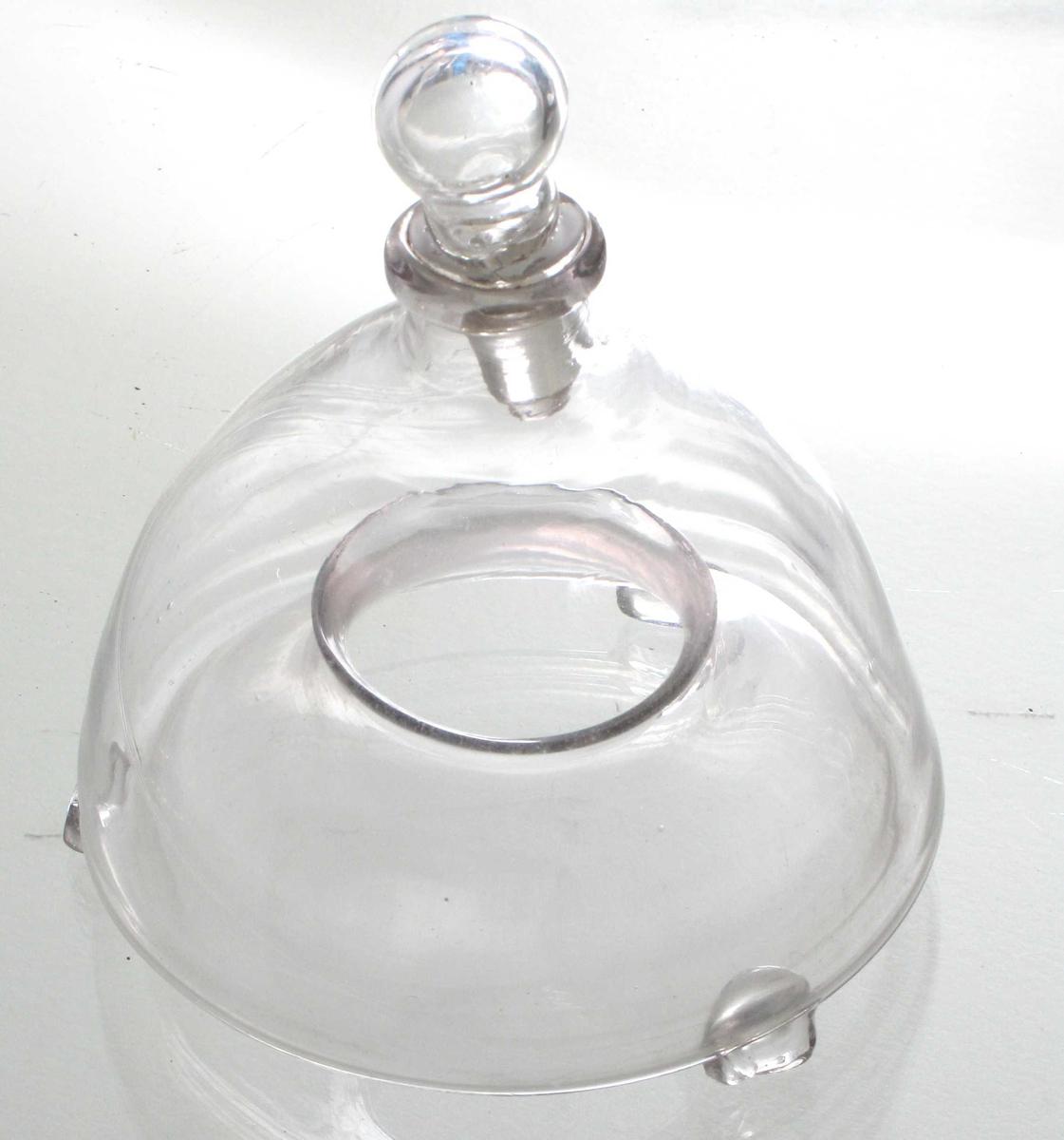 Klokkeformet beholder, tut med propp øverst, 3 lave bein ved nedrekant. Bunnen er bøyd innover og oppover i beholderen og har et hull i midten.