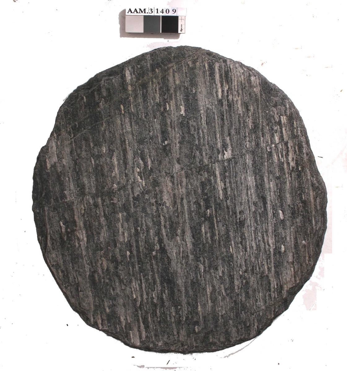Oval helle, av grålig gneis, fint tilhuget rundt hele kanten.  Hella er så godt som flat (antydning til konveks på en side og konkav på den andre), og i svært god stand.