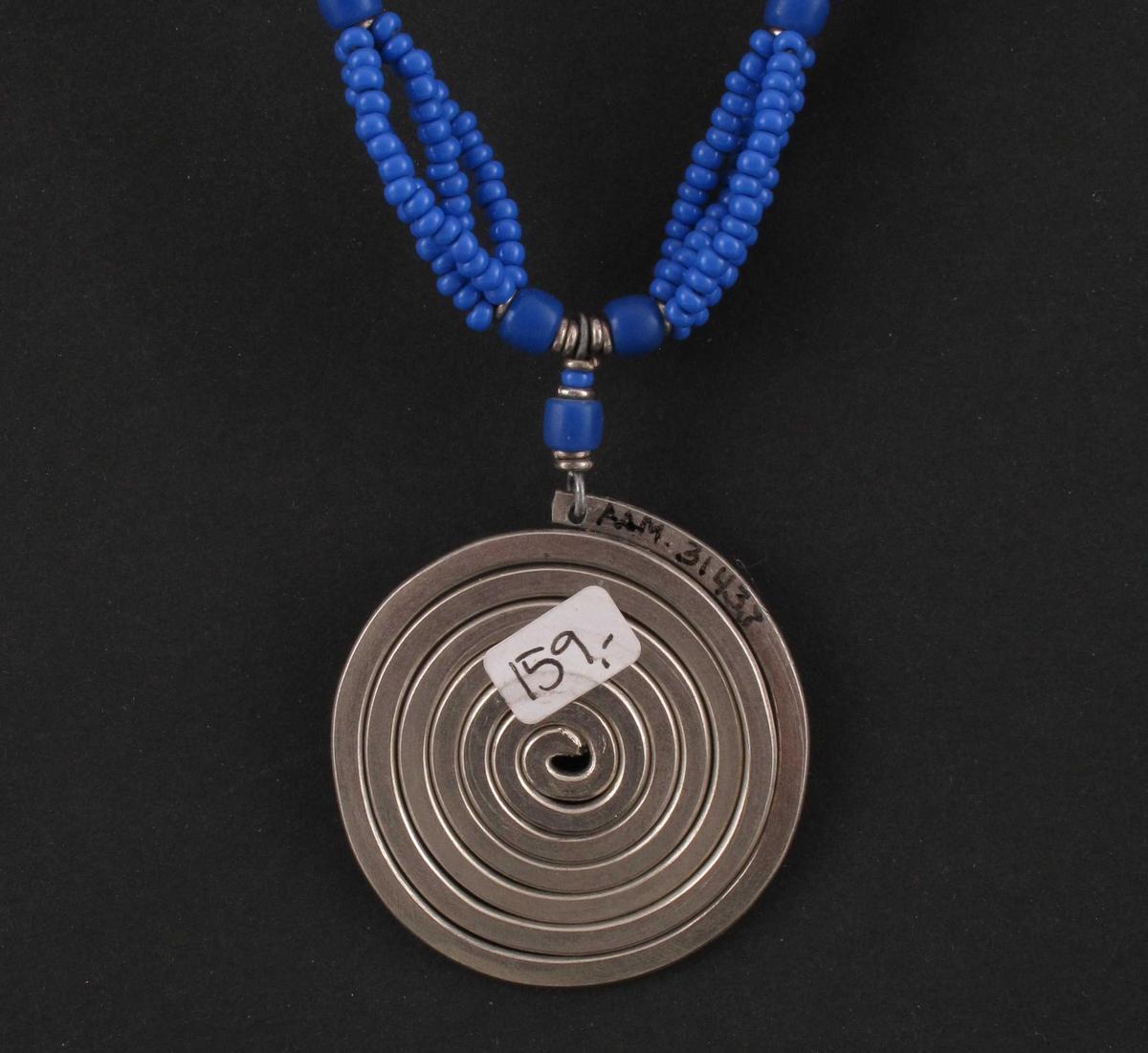 Perlekjede med anheng. Kjedet består av fire tråder med påttredde blå plastperler.  Fra låsen og 10,5 cm ned en enkelt rad perler, deretter en større perle.  Etter den fire strender med perler i en lengde på 4 cm, før de igjen samles i en større perle.  Til sammen 4 slike partier med fire strender før midten, hvor det henger et anheng i stål formet som en tett spiral.  Samme rekkefølge med perler på andre siden av spiralen.  På hver side av de blå perlene er det små sølvfargede metallringer.  Påklistret prislapp pålydende 159,-