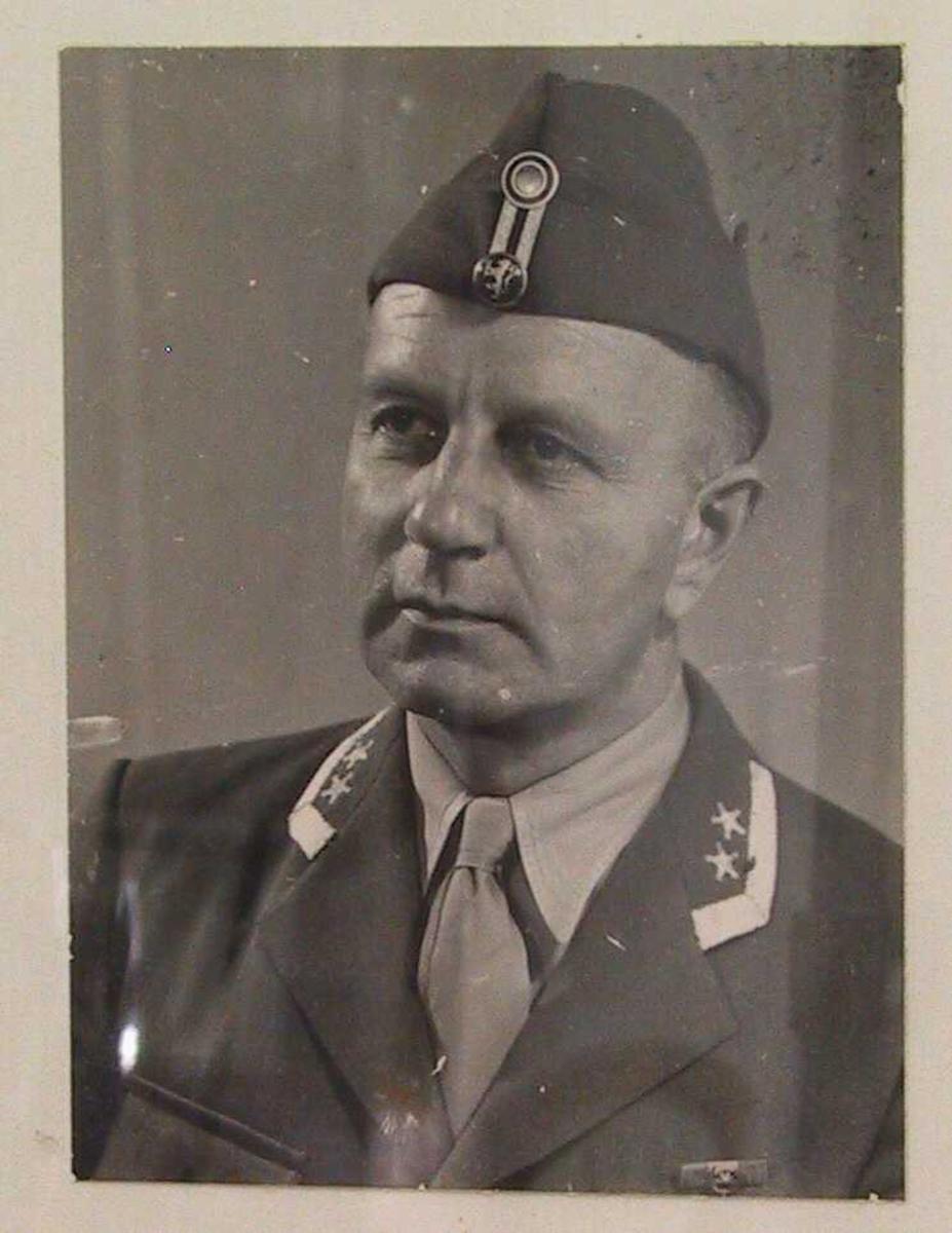 Portrett av  Harald Juell i oberstuniform, ca. 1947.  Brystbilde, halvt venstrevendt,  hodet litt bøyd mot høyre  Alliert uniform med lue. Anta. tatt i Tyskland. hvor Juell var oberst i  de allierte okkuasjonsstyrker etter krigen.