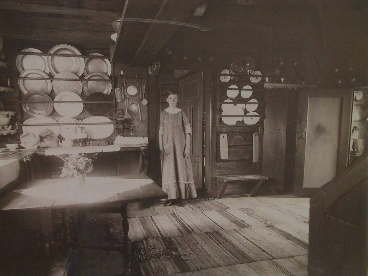 Fotografi av kjøkkenet på Merdøgaard, med hushjelp Laura Hansen, Merdø, står i døren ut til gang mot bryggerhuset.  Kjøkkenet sett fra gangdøren, med rekker og husgeråd på veggene.