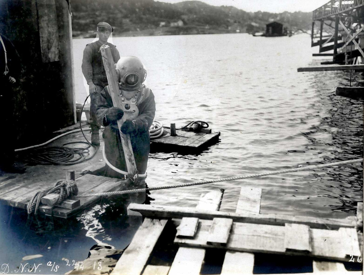 """""""22/04-1913"""" Nitriden. Dykker og pumpemann i arbeid ved kaianleggene ved Tromøysund. Tromøy i bakgrunnen."""