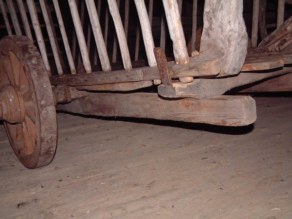 Understell av to langsgående trebjelker. På disse ligger en treaksling med firkantet tverrsnitt og to tverrstykker. Overdelen hviler på akslingen og tverrstykkene. Naturlig kroket trevirke i fram- og bakkar. To hekker med loddrette spiler, 17 på den ene og 16 på den andre siden. Hekkene hviler nedi vinkeljern. Bunn av fire planker.På utsiden av fram- og bakkar er det kroker for feste av bendestangen.