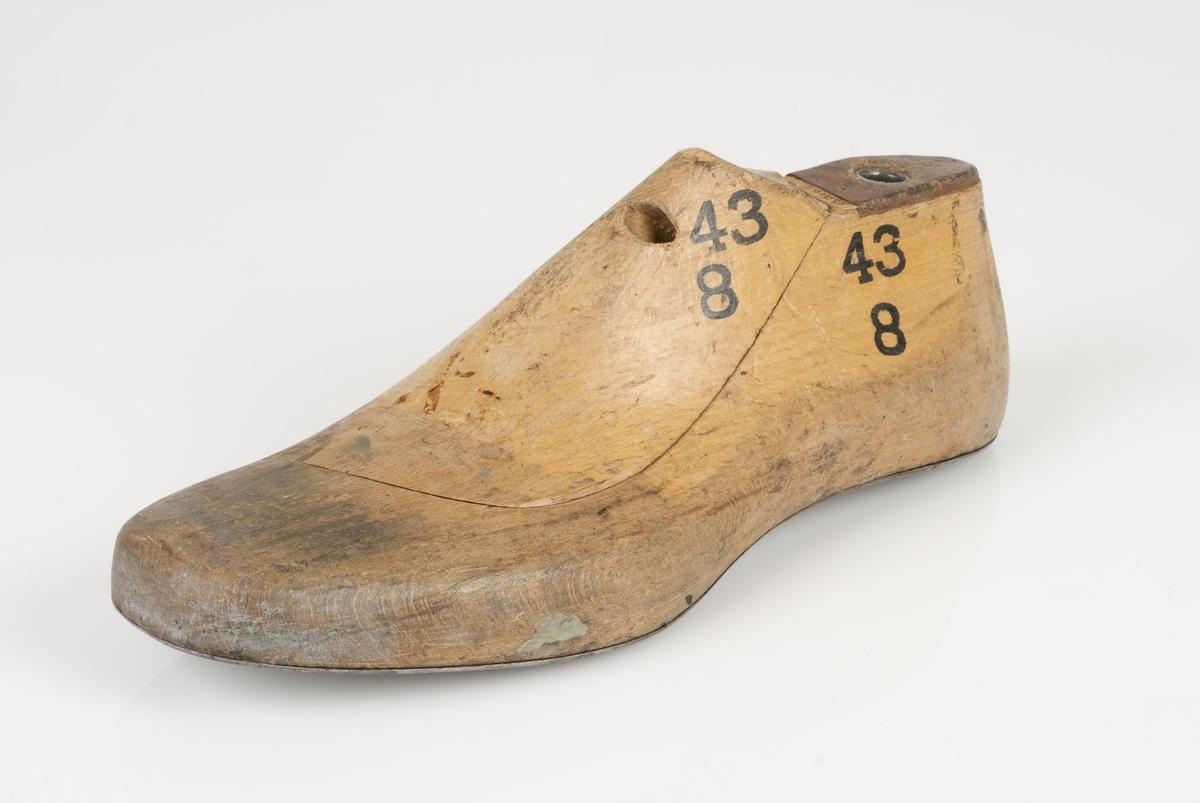 En tremodell i to deler; lest og opplest/overlest (kile). Venstrefot i skostørrelse 43, og 8 cm i vidde. Såle i metall. Lestekam i skinn.
