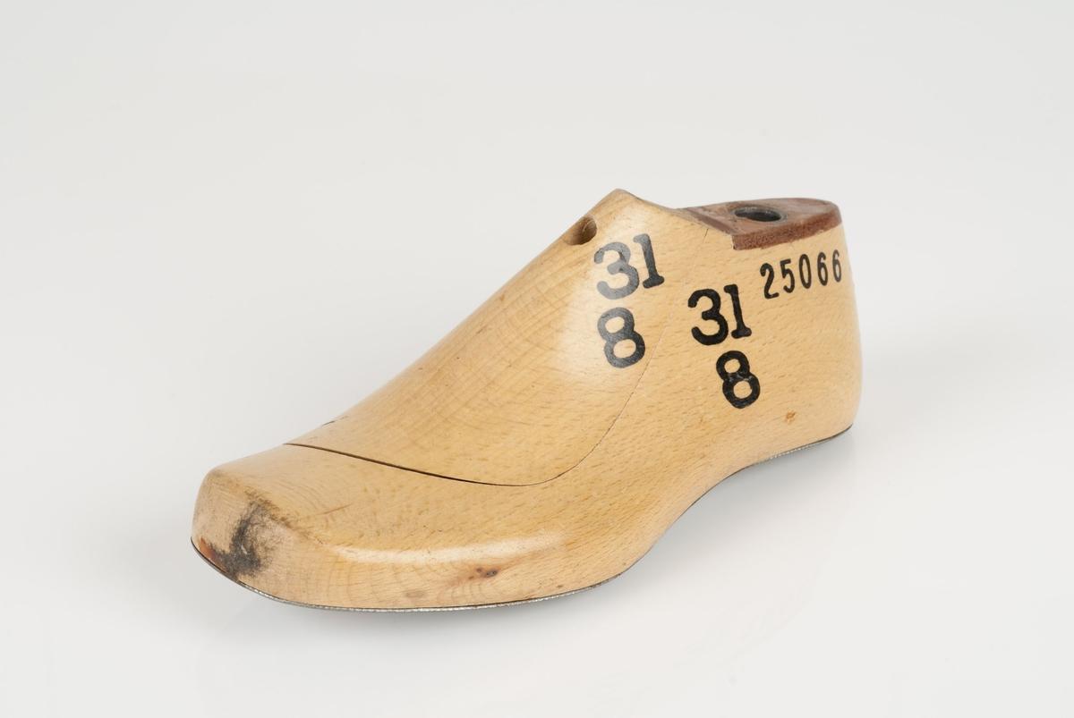 En tremodell i to deler; lest og opplest/overlest (kile). Venstrefot i skostørrelse 31, og 8 cm i vidde. Lestekam i skinn. Såle i metall.