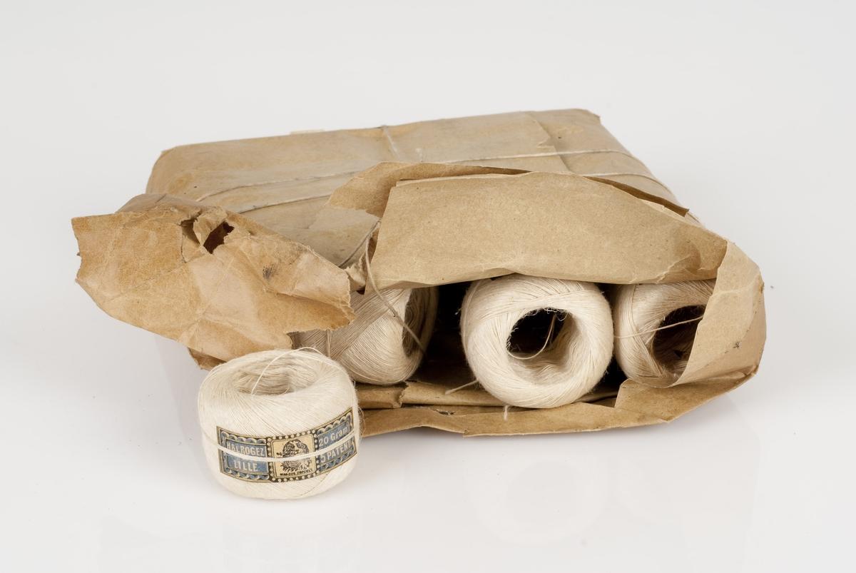Tynn hvit lintråd i rull. Trådrullene har påklistret merkelapp med påført tekst. Rullene ligger samlet i en papirpakning bundet sammen med hyssing. Pakningen er revet opp på den ene enden, og har en påklistret merkelapp med påført tekst på den andre enden (underenden).
