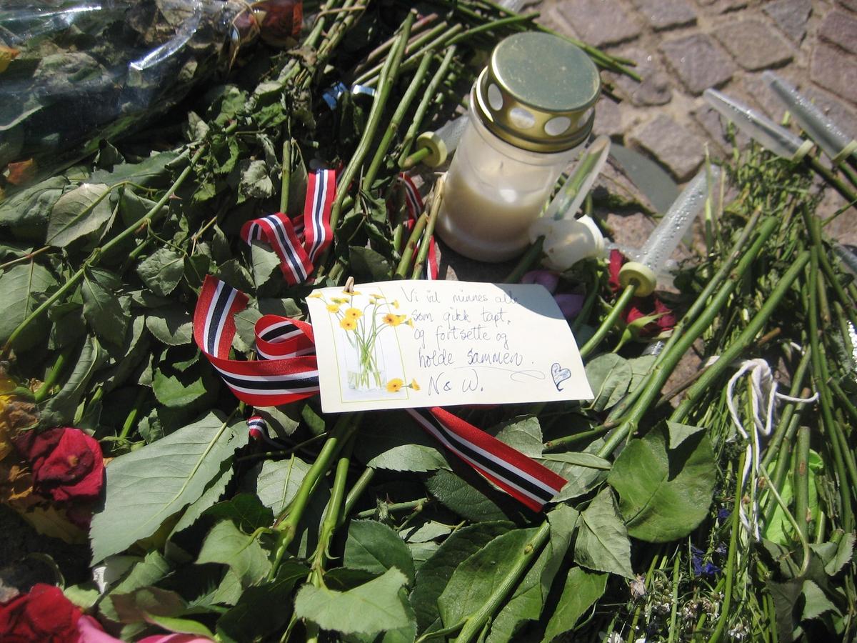 Minner etter terrorhandlingen den 22. juli 2011. Blomster, kort og lykte på fontene på Lillestrøm torg.