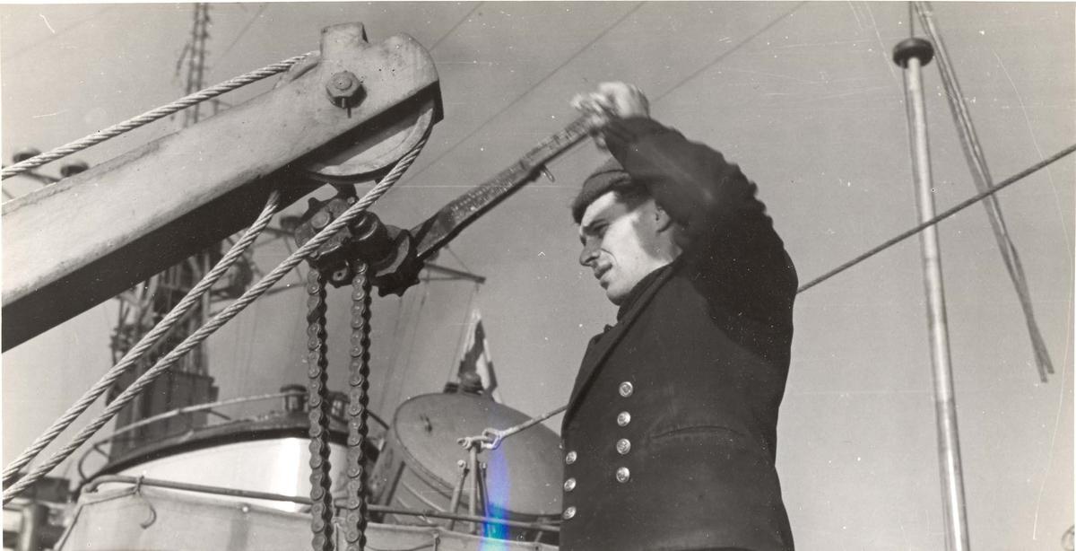 Enkeltbilde. Jageren Stord i konvoy til Murmansk. En av mannskapet jobber med kranen ombord, som ofte blir brukt til heising av dypvannsminer, torpedoer og utstyr