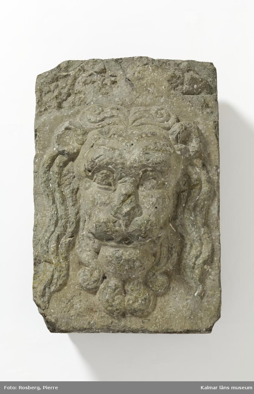 KLM 12225. Byggnadsdetalj, lejonmaskaron. Av grå kalksten.  I form av en lejonmask i hög relief. Lejonet har lång, vågig man med markerade ansiktsdrag. Stenen har spår av vit färg och murbruk.