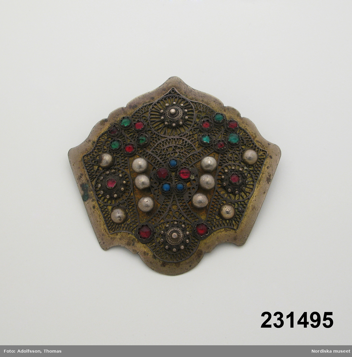 """Huvudlggaren: """"Smycke, brosch av vit svartnad metall, sköldformigt utformad, filigranliknande beläggning samt infattade blå, gröna och röda stenar, nitliknande prydnader. Enl. testamente."""""""